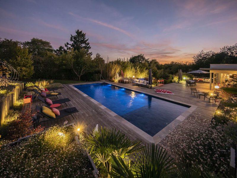 piscine entouré de terrasse en bois ambiance de nuit