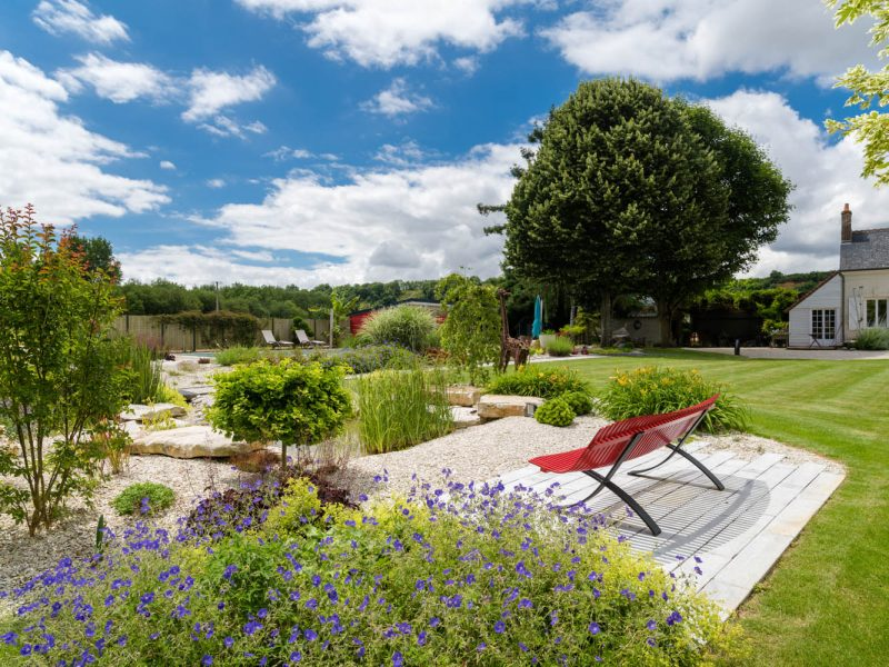 jardin et bassin avec banc fermob coloris coquelicot et terrasse en dallage
