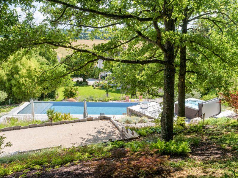 massif de sous bois avec piscine paysagée en second plan