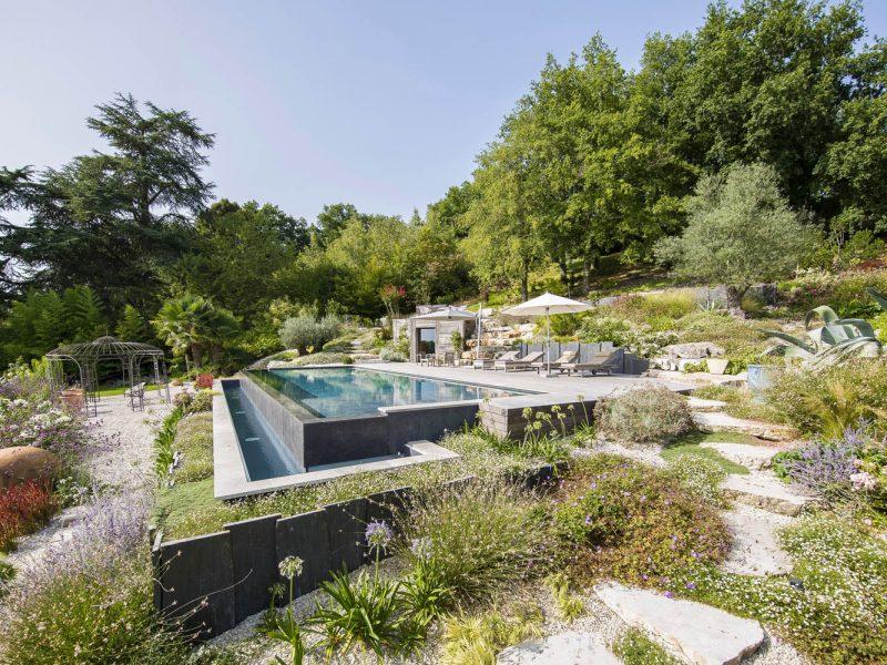 piscine à débordement paysagée avec marche en pierre et terrasse bois