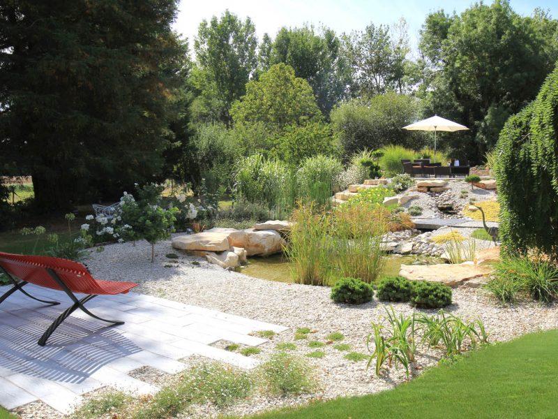 bassin avec terrasse en dallage et banc fermob coloris coquelicot