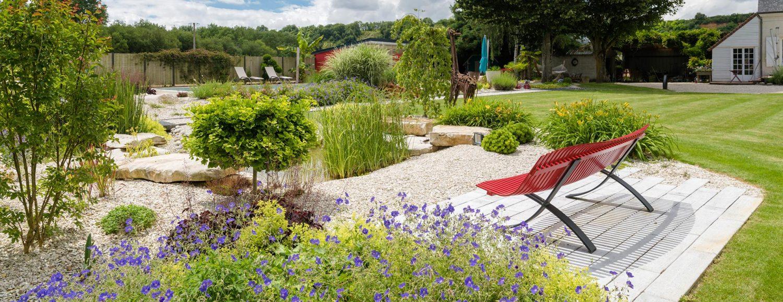 banc rouge avec des massifs fleuris et un bassin naturel