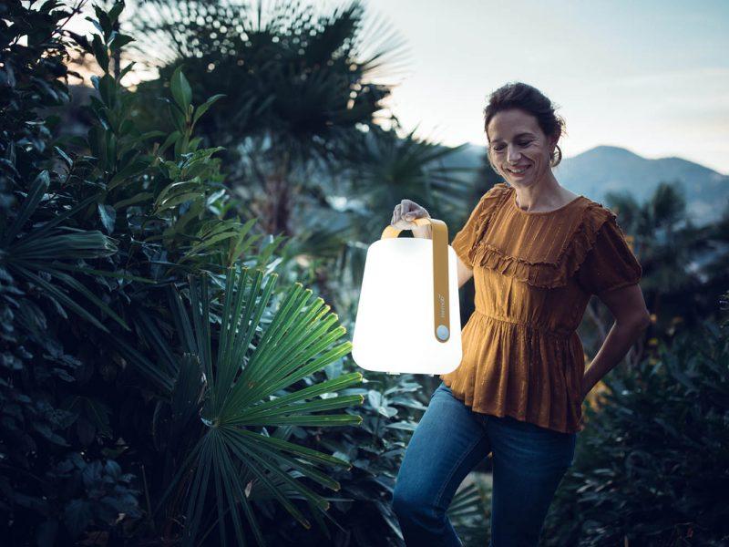 femme portant une lampe fermob modèle ballad