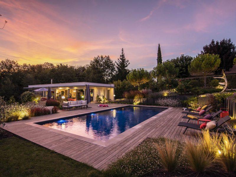 piscine vue de nuit avec terrasse en bois et éclairage dans les massifs